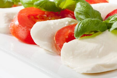 A detail shot of mozzarella and tomatoes garnished with basil  photo