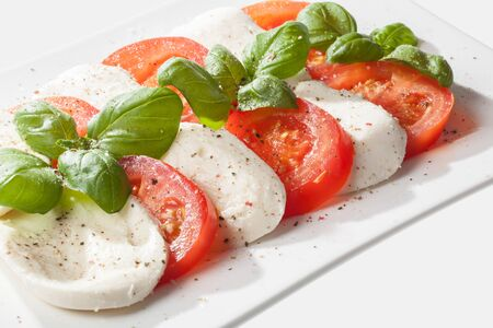 A plate of tomatoes and mozzarella decorated with some basil  photo