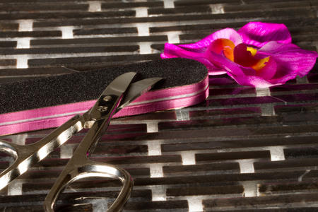 A nail scissors with a nail file on a highlighted floor  photo
