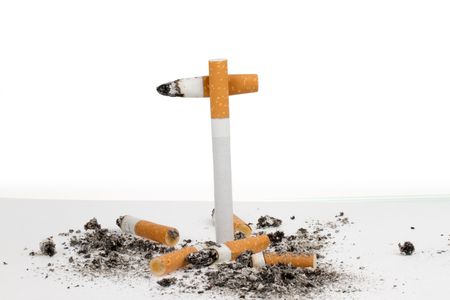 A crux is build with cigarettes where other used cigarettes are lying on the floor  photo