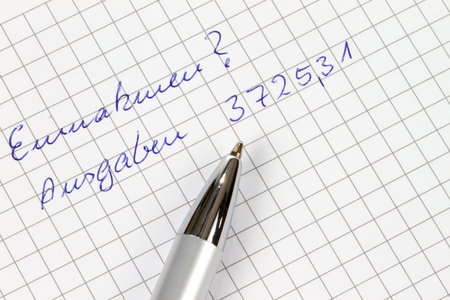 outgoings: Earnings and outgoings are written in german on a checked paper decorated with a pen