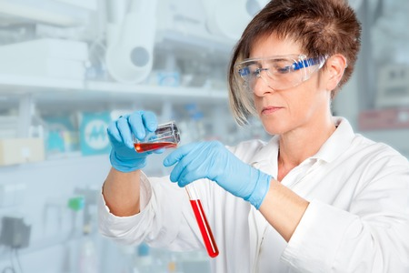 A Chemist student is decanting a red liquid into a test tube in her laboratory  photo