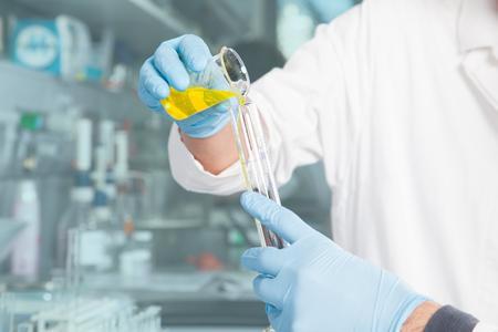 A Professor is preparing a chemical yellow liquid mix  Stock Photo