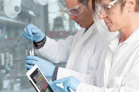 medical gloves: A Doctor is using a periodic table of the elements on her mobile device