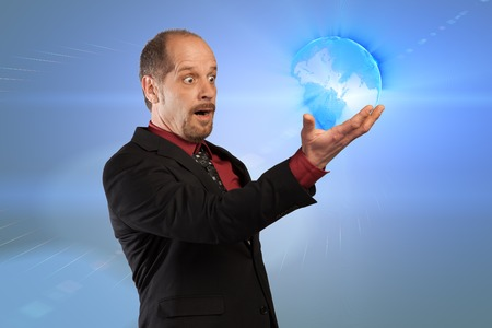 A Businessman is looking to a glowing earth in his hands  photo