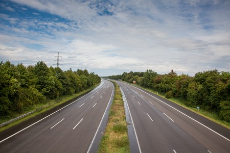A german Highway without any cars. The Road is wet from the rain but the Sun is coming up again. Stock Photo