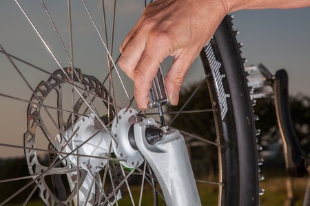 tightly: A woman is screwing tightly the fork at her bike. The Bike is in upside down position.