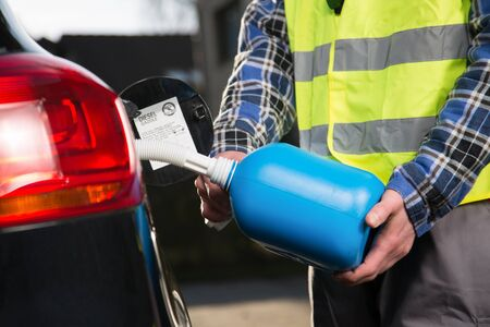 A man with a reflective vest is fueling a vehicle with a plastic canister.