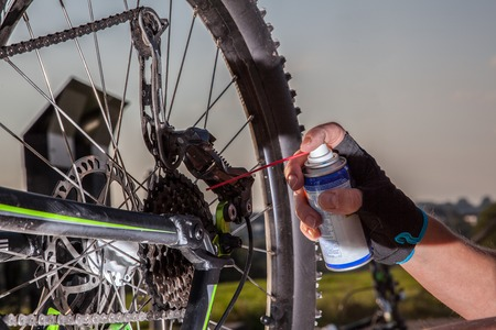 mountainbike: A man is oiling the chain from his mountainbike.