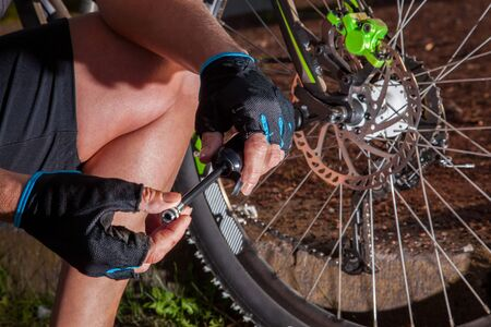mountainbike: A man is verifying the air pressure on his mountainbike.
