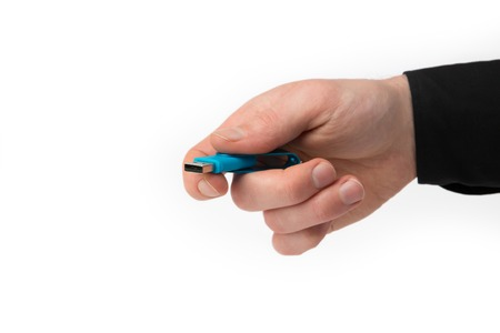 A Hand from a Businessman holds a USB Stick isolated on a white background. photo