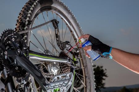 Een man is met behulp van een olie spray om de ketting van zijn mountainbike smeren .. Stockfoto