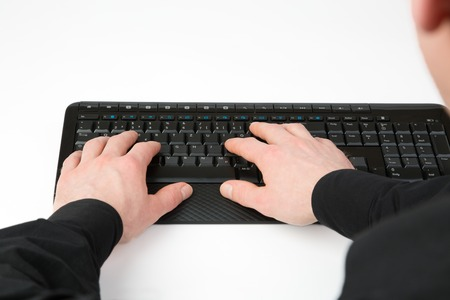 over the shoulder view: An over shoulder view from a businessman to a black Computer Keyboard, isolated on white