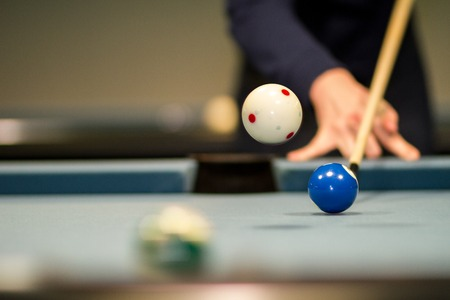A jump shot on a blue Pool Billard table.