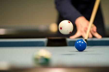 A jump shot on a blue Pool Billard table.