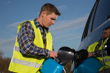 emergency vest: A man is refilling his car from blue gas canister on the street.