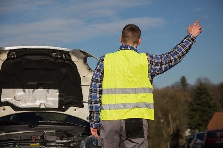 A young man asks for help on the road near his broken car