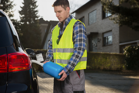 emergency vest: Man pouring fuel into gas tank of his car from blue gas canister on the street.