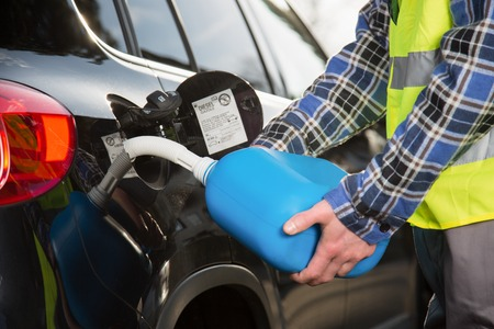 A young man is refueling a vehicle with a blue plastic canister. Stock Photo