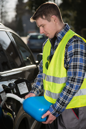 emergency vest: A young man is refueling his car with a blue plastic canister.