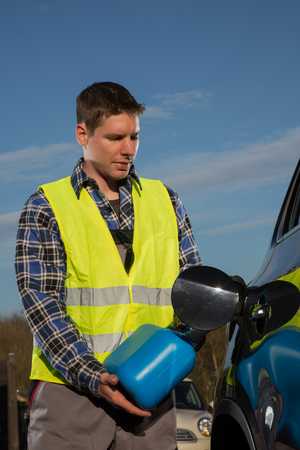 emergency vest: A young man is refueling his car with a blue plastic canister at a sunny day. Stock Photo