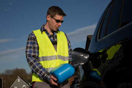 emergency vest: A young man dressed with an reflective vest is refueling his car on the road with a blue canister.