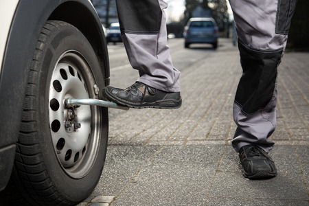 tire fitting: A man is loosening the screws from the tire. Stock Photo