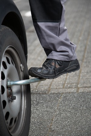 tire fitting: A mechanic tries to unscrew the tire screws with the foot to do a tire change.