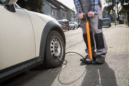 malfunction: A man is pumping up a car tire after a malfunction