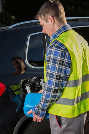 emergency vest: A young man with an reflective vest is refueling his car with a blue canister. Stock Photo