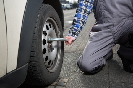 tire fitting: A mechanic solves the nuts of the autowheel to change the tire.