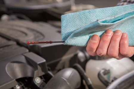 A mechanic is checking the oil level from a car engine. photo