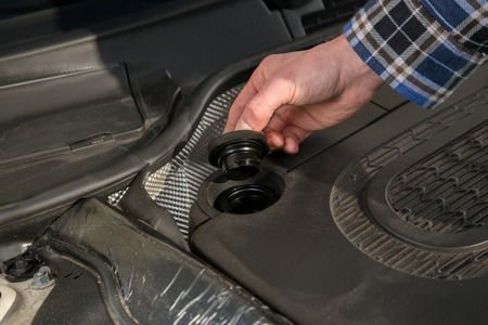 A mechanic is opening the oil cap from a car engine. photo