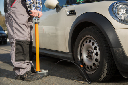 malfunction: A man is refilling the car tire after a malfunction.