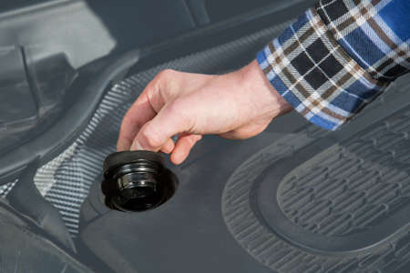 A mechanic opens the cap in the car engine block. photo