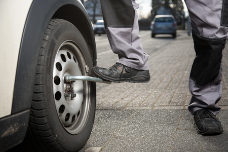 tire fitting: A mechanic is unscrewing a tire screw with the help of his feet.