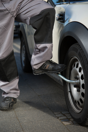 tire fitting: A man is changing a car tire with the help of his  feet