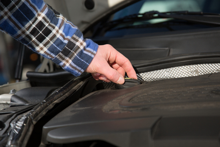 A man is opening a oil cap inside a car engine motor block. photo
