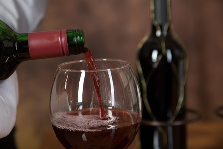 waiter: A Waiter is pouring red wine into a glass with a bottle of red wine in the background.