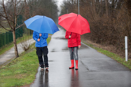 rain boots: Una pareja est� caminando a trav�s de la lluvia con paraguas y ropa de lluvia.