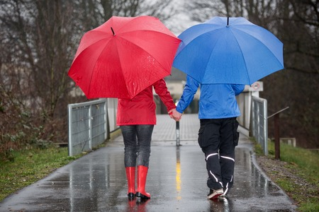 A young couple is walking hand in hand in the rain through a park.
