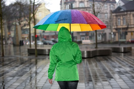 A woman is walking through the rain with an umbrella and green raincoat in the city.