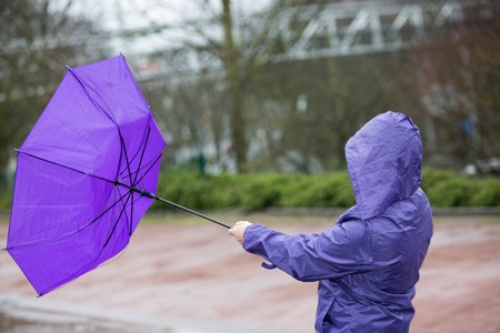 A lady is fighting with the umbrella while a storm is blowing. Stock Photo