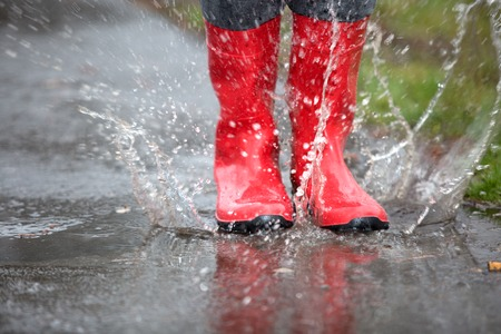 A pair of red rubber boots are jumping into a big puddle.