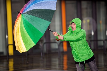 caucasian water drops: A woman is fighting against rain and wind.