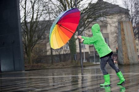 色の傘を持つ女性は、嵐に対して戦っています。