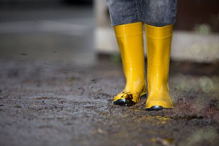 smut: A pair of rubber boots standing in a dirty puddle