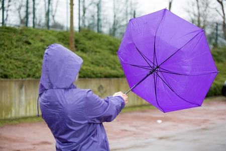 A people is fighting with an umbrella in the wind.