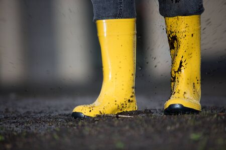 smut: A pair of yellow rubber boots in a dirty puddle
