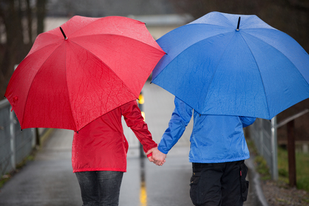 rain shower: A couple is walking hand in hand through the rain with umbrellas and rain cloth. Stock Photo